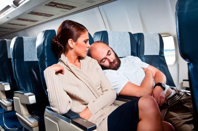 homem deitado em mulher no avião