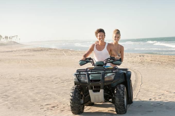 Casal dirigindo um Quad ATV na praia