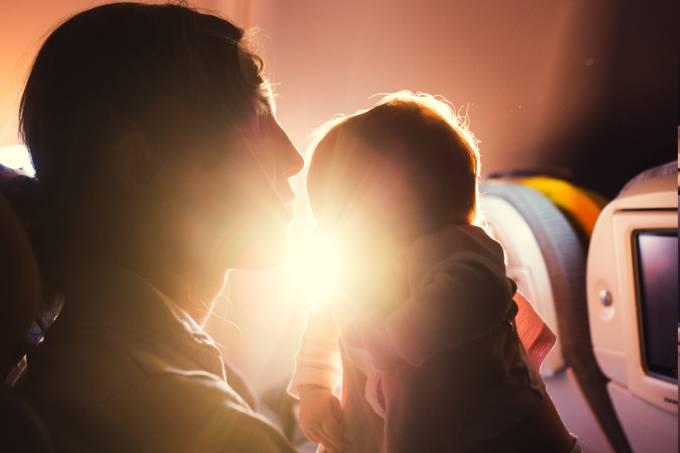 Mãe e bebê sentados em poltrona de avião durante voo comercial com sol ao fundo
