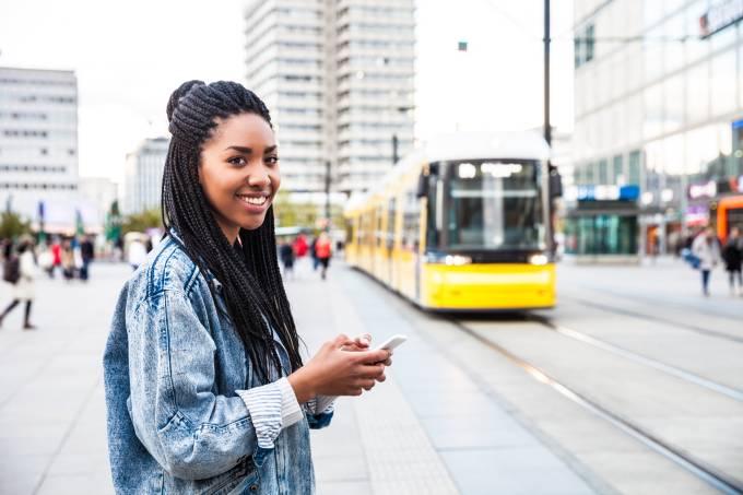 Mulher jovem caminhando com celular smartphone na Berlim Alexanderplatz