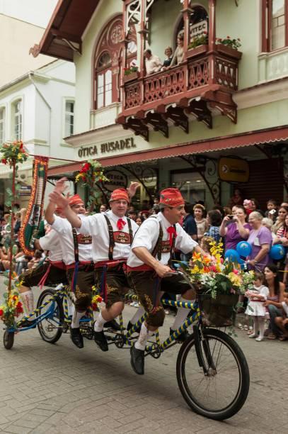 Grupo de amigos em uma bicicleta compartilhada durante uma evento de rua em Blumenau