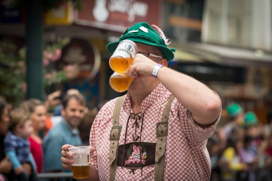 Homem bebendo três copos de cerveja durante o Oktoberfest, em Blumenau.