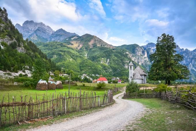 Cidade de Theth na Albânia, com estrada e igreja e montanhas ao fundo Foto alsem iStock-509737184