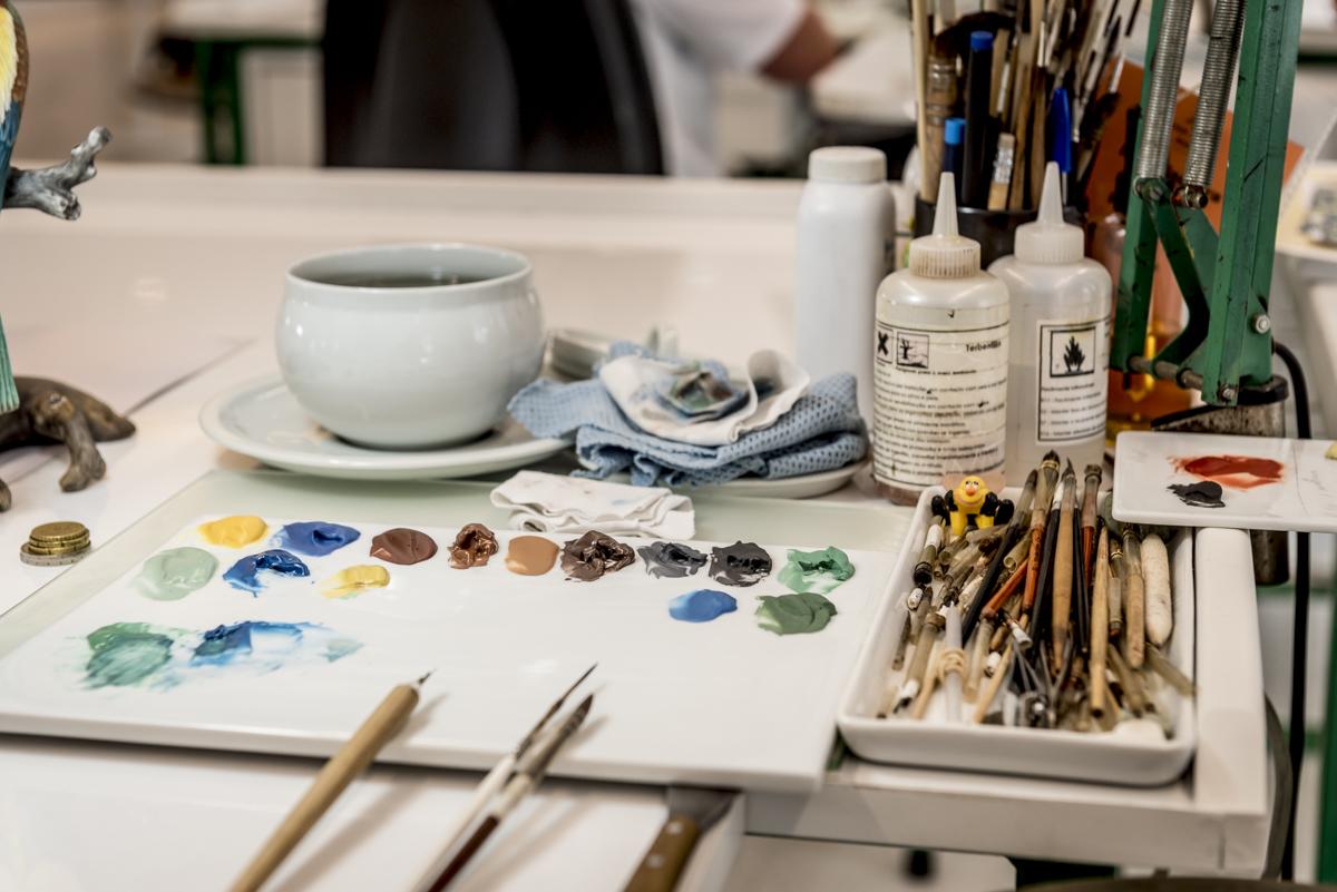 Detalhe das tintas e pincéis dos artistas: peças pintadas a mão ainda nos dias de hoje