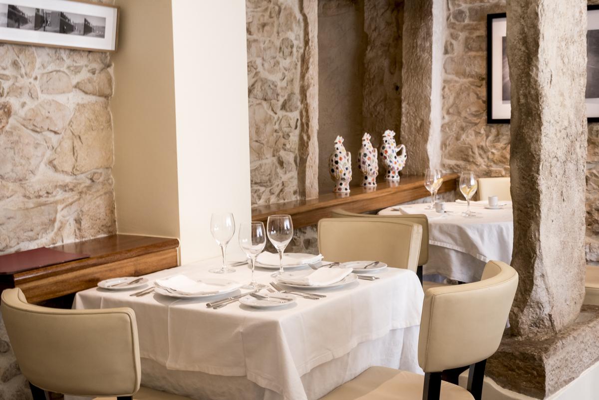 Um cantinho do restaurante: paredes de pedra, toalhas de linho e comida com alma