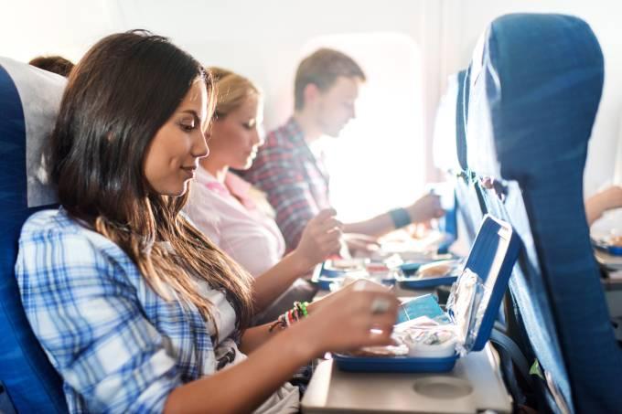Passageiros almoçando dentro do avião