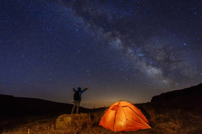 Homem e sua barraca em uma noite estrelada