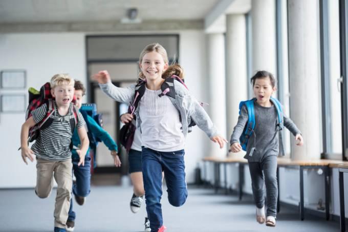 Crianças correndo de mochilas