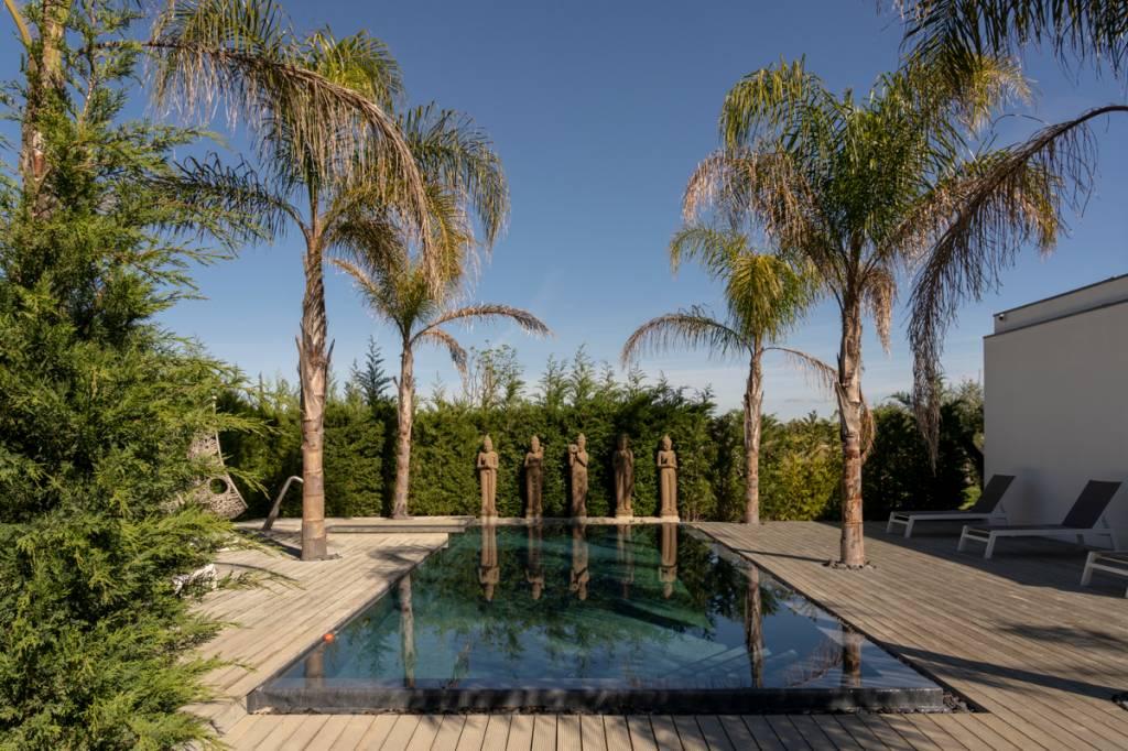 A piscina, escoltada por estátuas balinesas