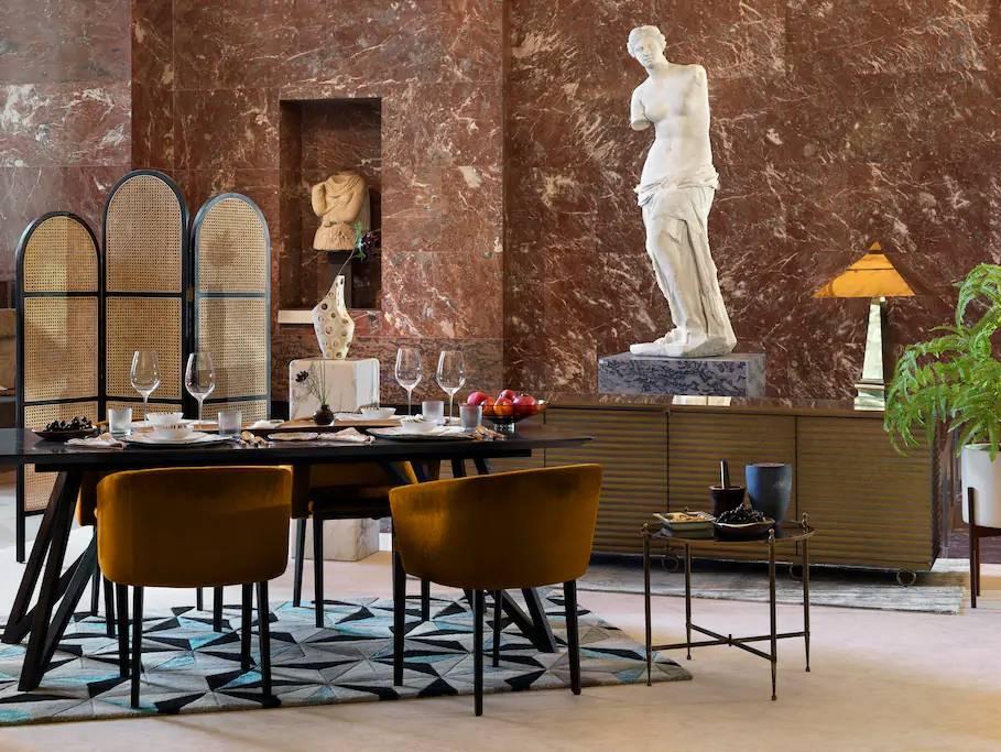 Mesa de jantar montada em frente a estátua de Vênus de Milo, no Museu do Louvre, em Paris