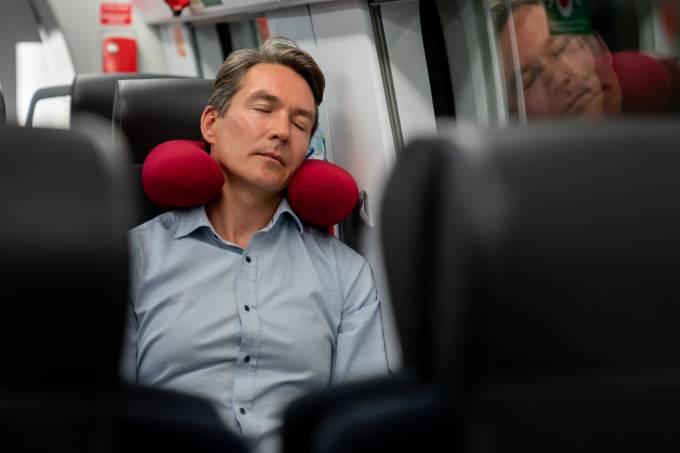 Homem dormindo com almofada de viagem