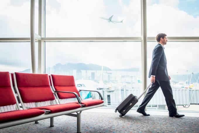 Homem de negócios carregando mala com aeronave ao fundo