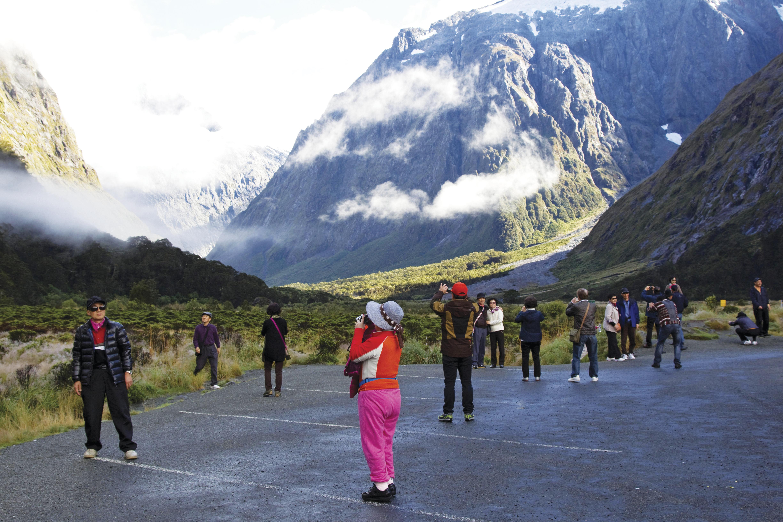 Turistas asiáticos em Milford Sound, Nova Zelândia