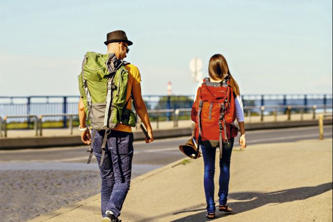 Duas pessoas andando com mochila nas costas