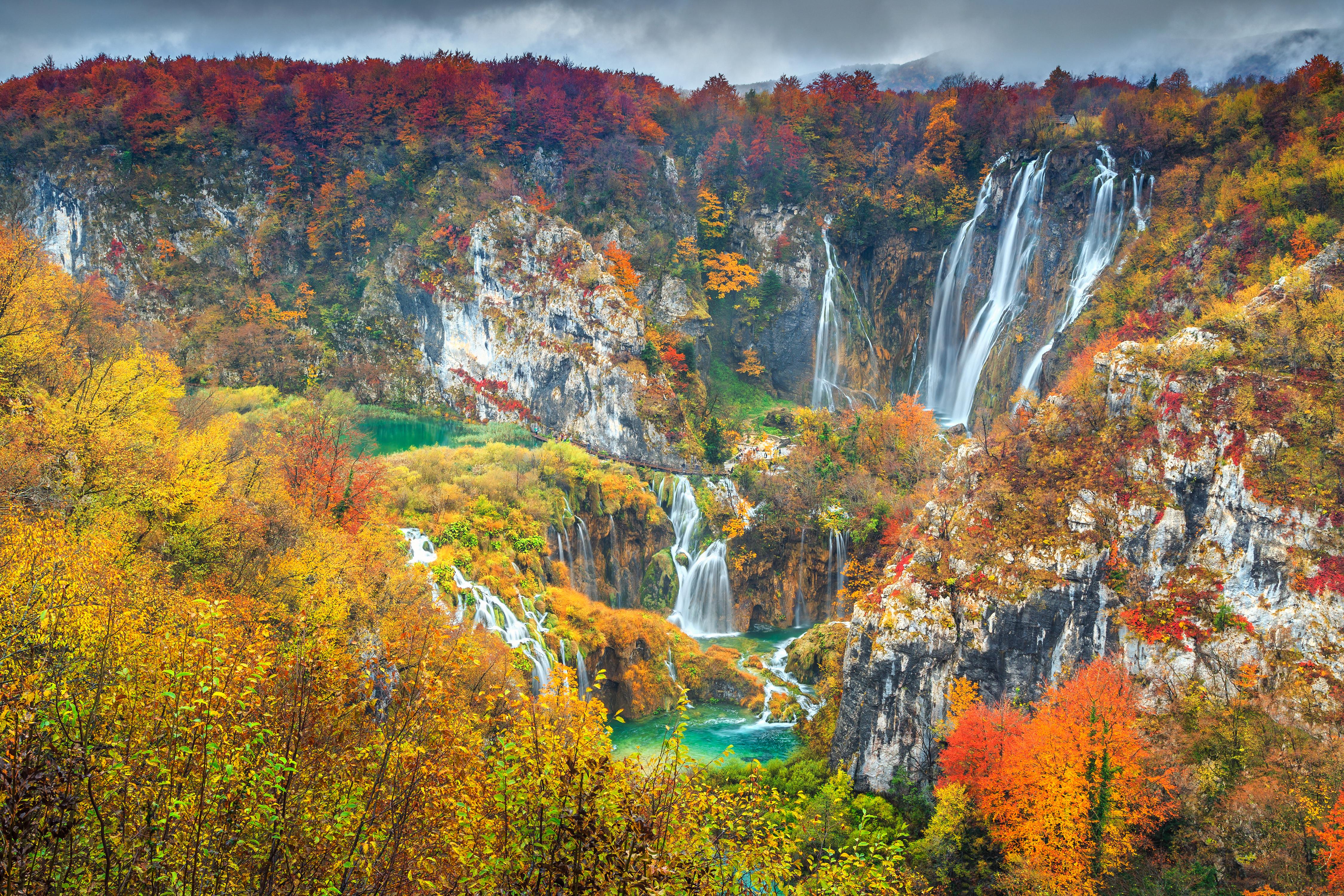 No outono, no Parque Nacional dos Lagos de Plitvice, o contraste entre as cores quentes e o azul dos lagos é surreal. Crédito: