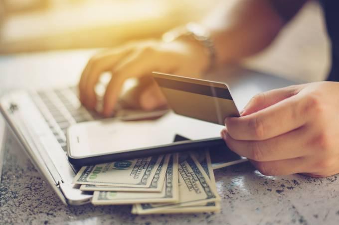 Pessoa com cartão de crédito e dinheiro no computador
