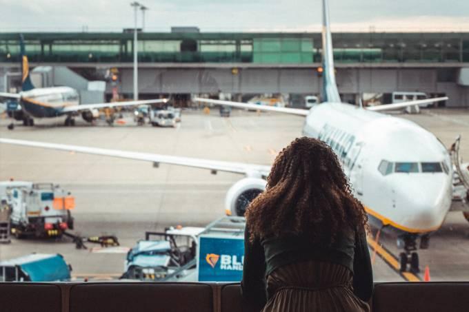 Mulher no aeroporto, olhando avião