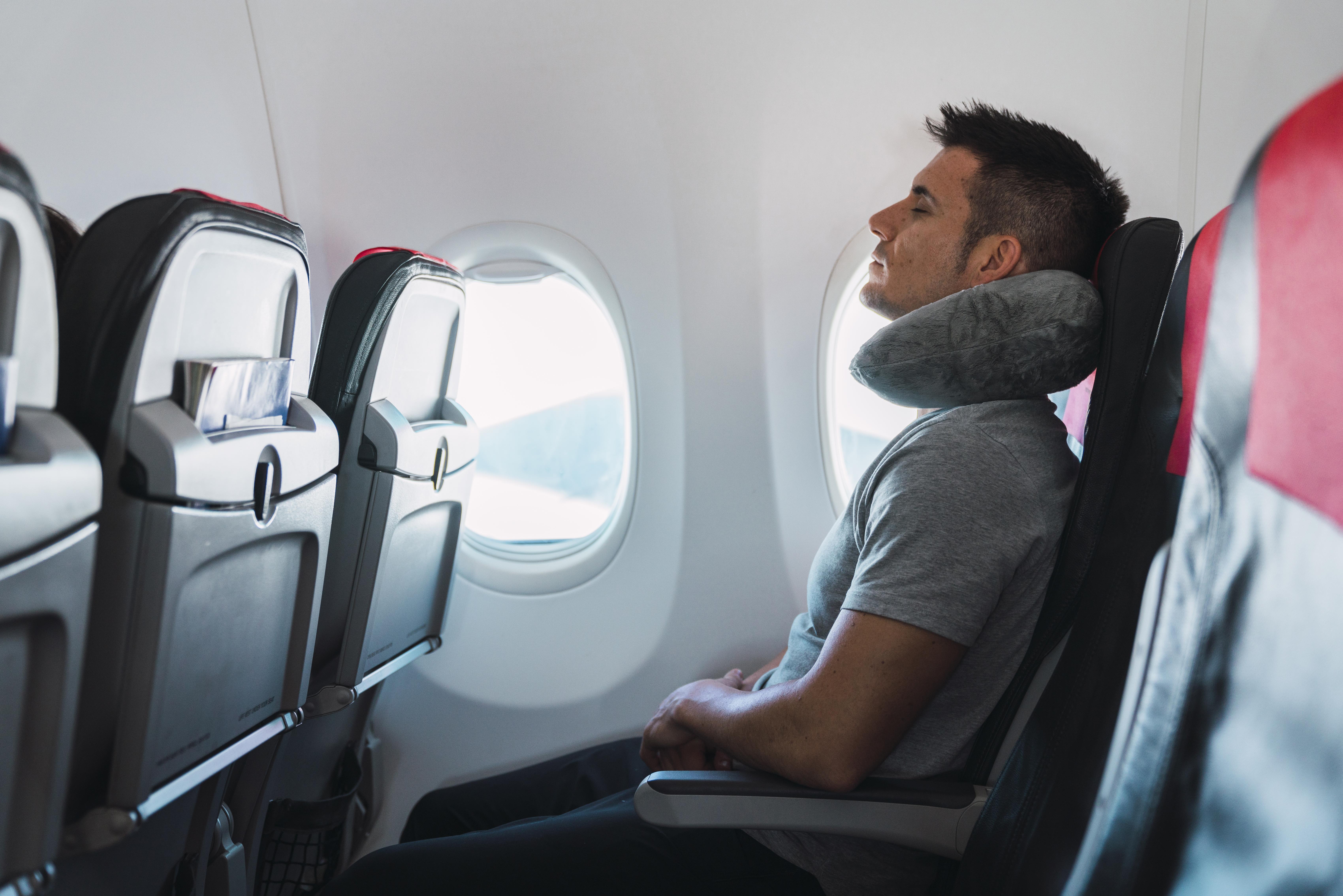 Homem no assento mais próximo a janela do avião