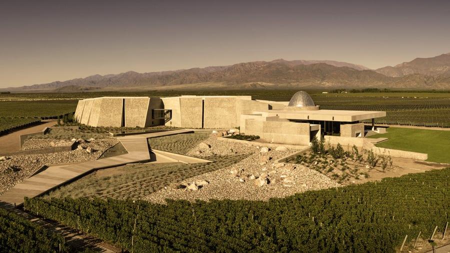 O cenário montanhoso ao redor dos vinhedos serviu de inspiração para a arquitetura da Zuccardi, toda feita com pedras da região. Crédito: