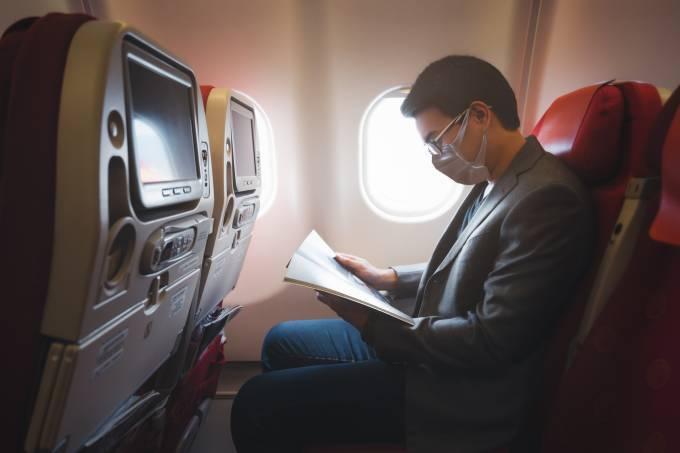 Pessoa de máscara no avião – coronavírus