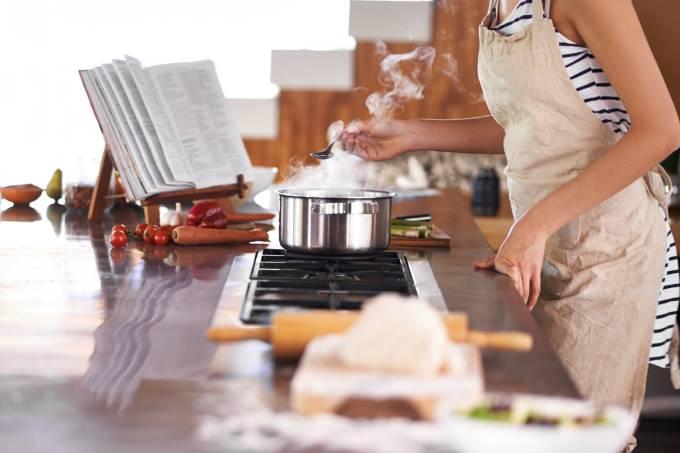 Mulher cozinhando com livro de receitas