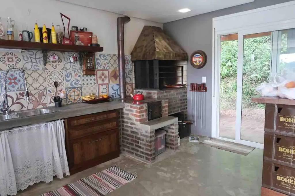 Nesta casa em Canela, o fogão campeiro se mistura a uma decoração contemporânea