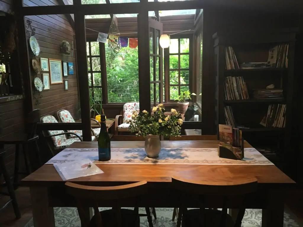 Sala de jantar com vista para o solário e o verde de chalé em Gramado (RS)