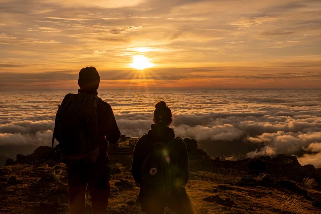 Duas pessoas observam o sol nascer acima das nuvens no Pico do Areeiro, Ilha da Madeira