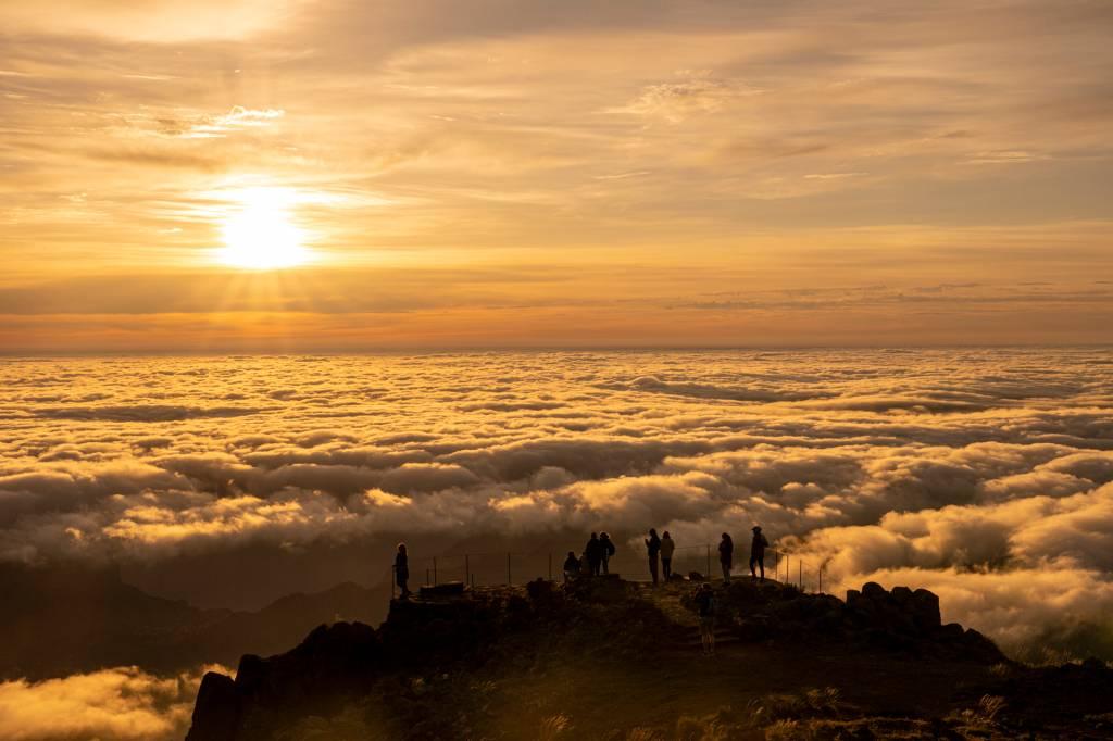 Pessoas assistindo o nascer do sol acima das nuvens no Pico do Areeiro, Ilha da Madeira