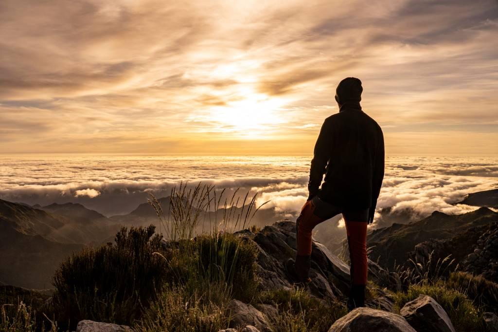 Homem observa o sol nascer acima das nuvens no Pico do Areeiro, na Ilha da Madeira