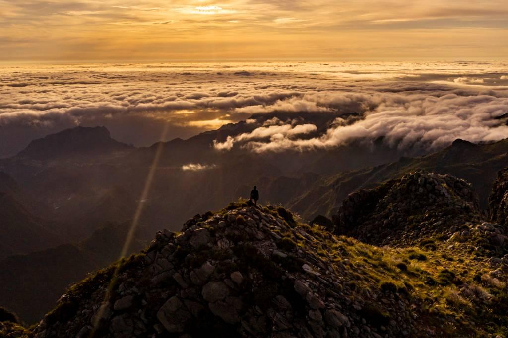 Pessoa sozinha no alto da montanha observa a paisagem acima das nuvens na Ilha da Madeira