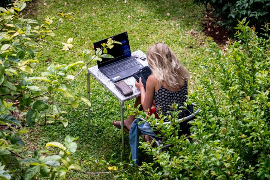 Mulher trabalha no computador em uma mesa no jardim do espaço de co-working da Digital Nomads, na Ilha da Madeira