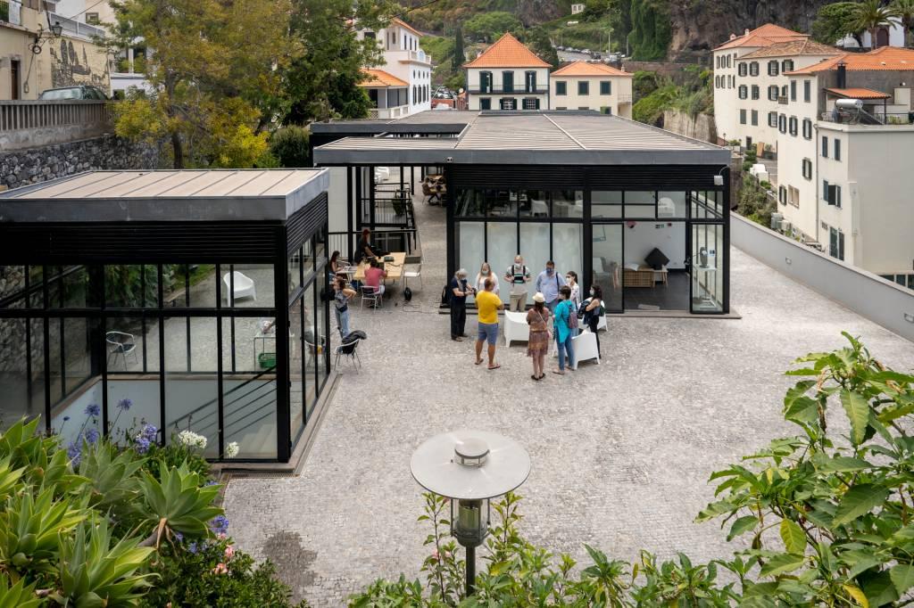 Vista aérea do espaço de co-working da Digital Nomads, com construções de vidro e jovens a conversar do lado de fora