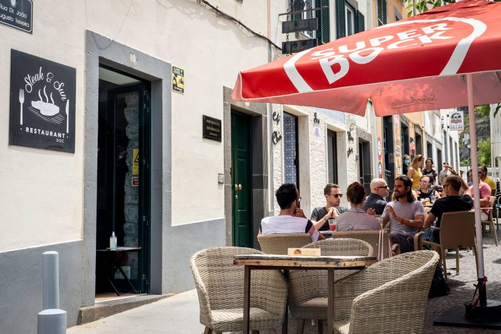 Restaurante com mesas ao ar livre debaixo de um guarda-sol vermelho