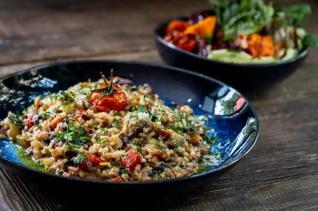 Risoto vegetariano de legumes em um prato azul sobre uma mesa de madeira