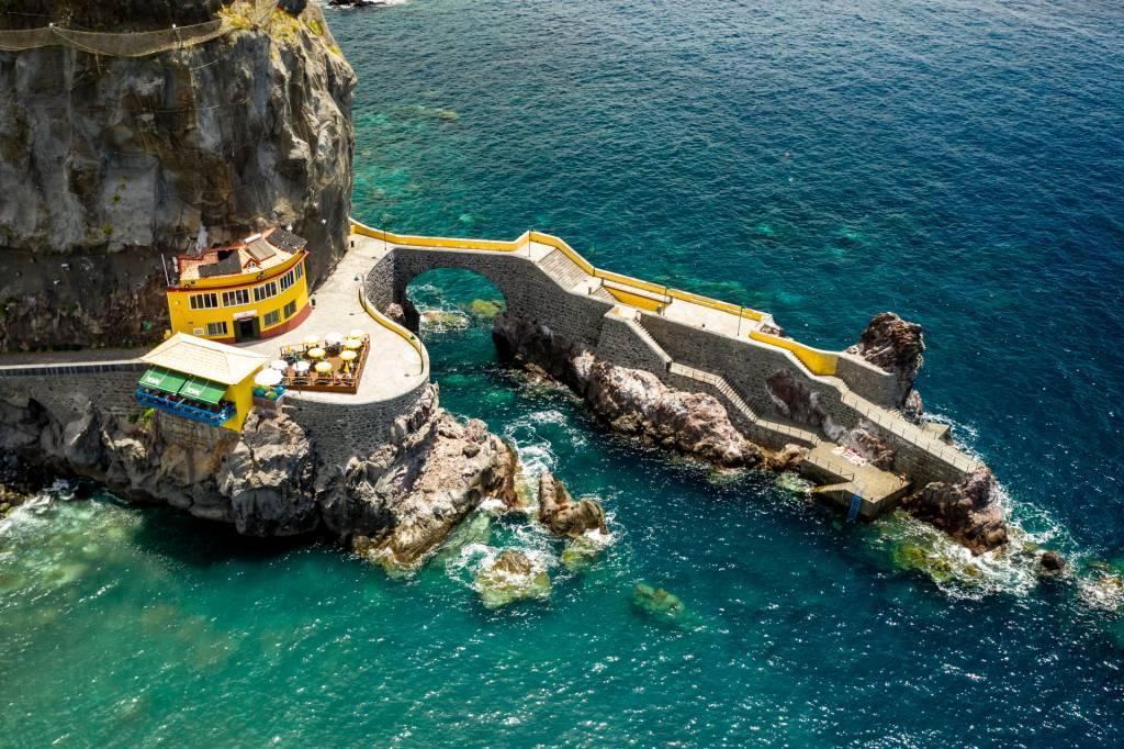 A beira-mar na vila de Ponta do Sol, com uma construção amarela sobre a falésia e pedras no mar, de cor verde esmeralda