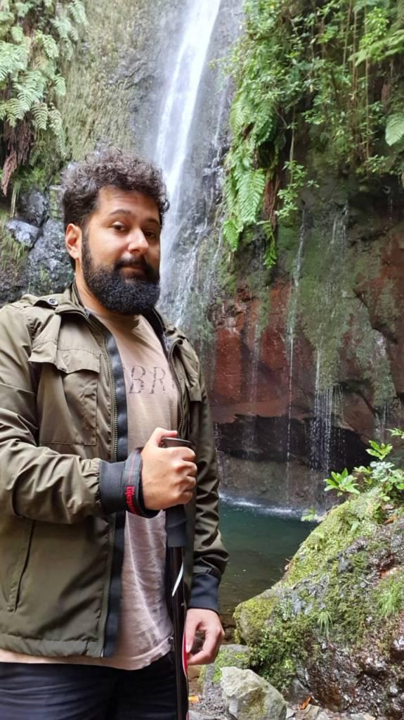 O designer brasileiro João Vicente em frente a uma cachoeira numa trila pela Ilha da Madeira