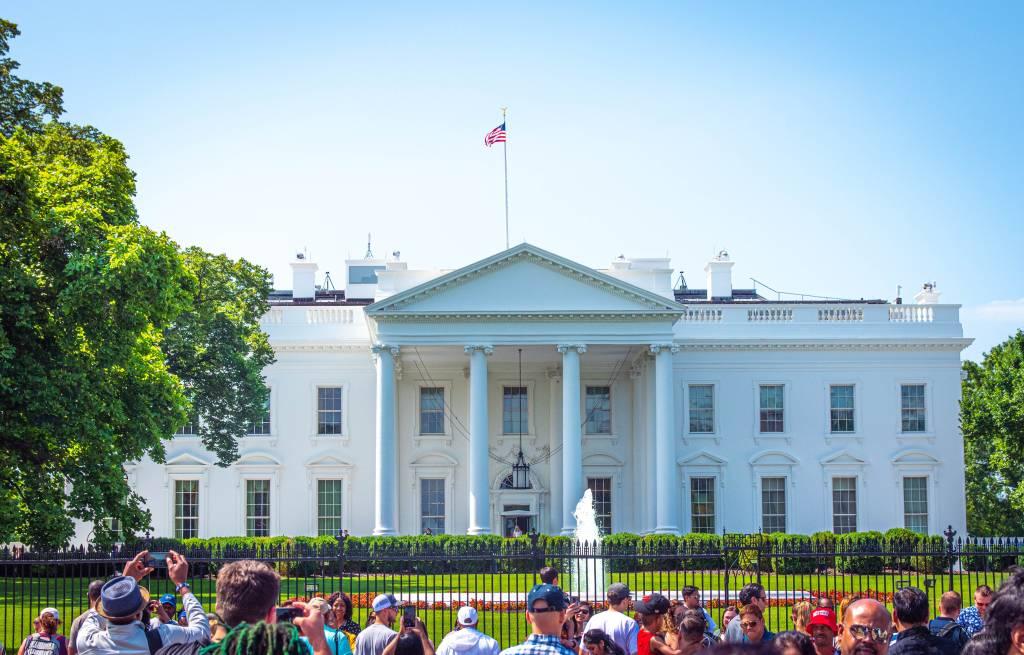 Turistas posam para fotos em frente aos portões que cercam a Casa Branca, em Washington D.C.