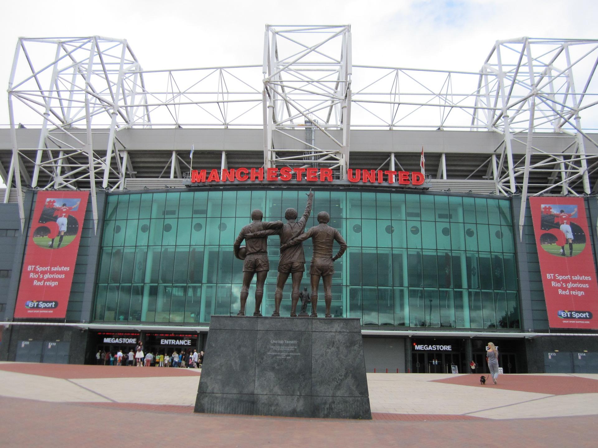 Entrada do estádio de Old Trafford, com a estátua dos jogadores George Best, Denis Law e Sir Bobby Charlton