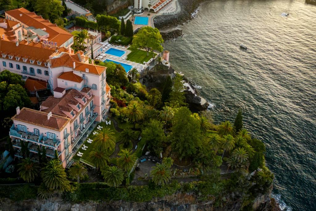 Vista aérea do hotel Reid's Palace, com o palacete rosa, duas piscinas e o jardim botânico debruçados sobre o mar