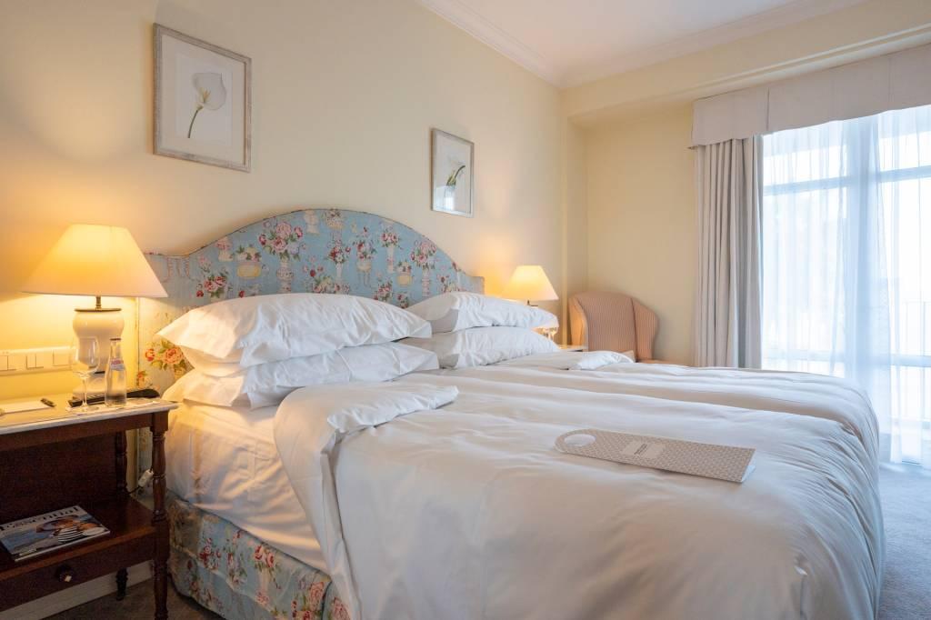 Quarto do hotel Reid's Palace, na Ilha da Madeira, com detalhe da cama com travesseiros, edredons e a cabeceira azul florida