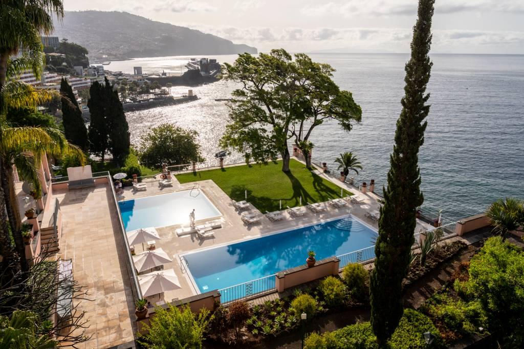 Duas piscinas, uma árvore e o mar no hotel Reid's Palace, na Ilha da Madeira