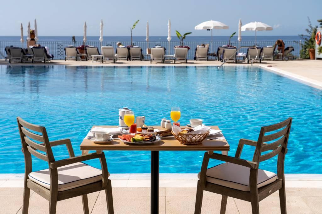 Mesa de café da manhã à beira da piscina do hotel Reid's Palace, na Ilha da Madeira, com duas cadeiras e espreguiçadeiras ao longe