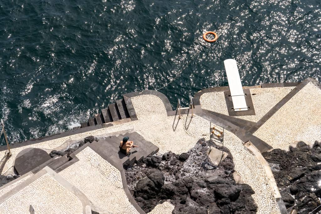Beira-mar do hotel Reid's Palace, na Ilha da Madeira, com pedras e uma plataforma com escada e trampolim