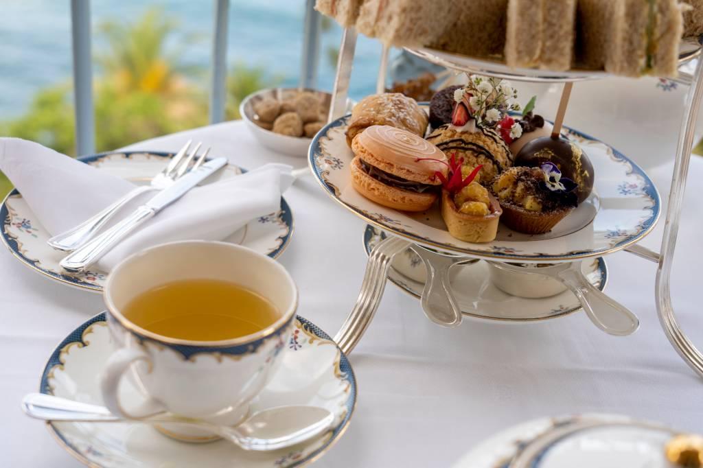 Xícara de chá e prato de doces em cima de uma mesa com vista do mar no hotel Reid's Palace, na Ilha da Madeira