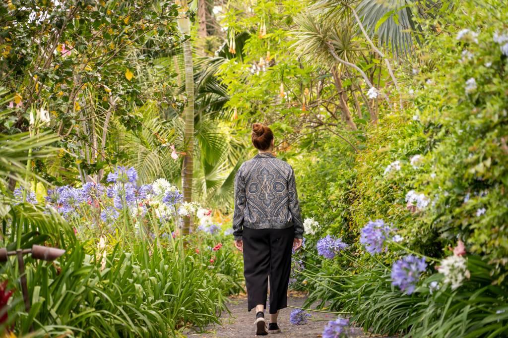 Mulher caminha pelo jardim do hotel Reid's Palace, na Ilha da madeira, entre plantas verdes, flores roxas e árvores