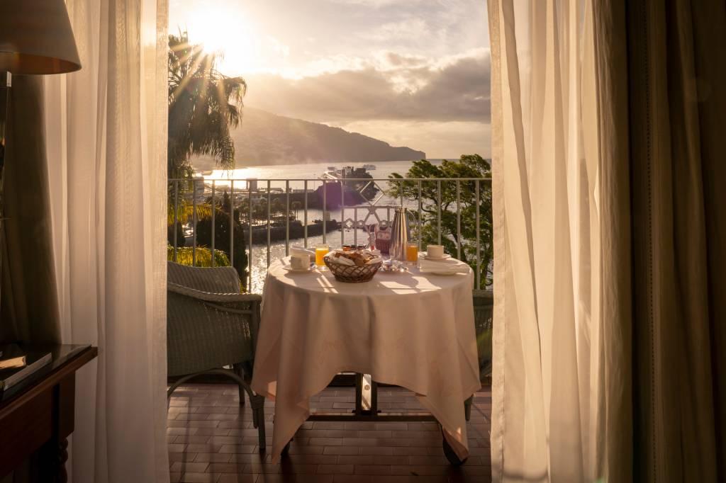 Mesa posta com o café da manhã e duas cadeiras na varanda de um quarto do hotel Reid's Palace, na Ilha da Madeira, com vista do mar