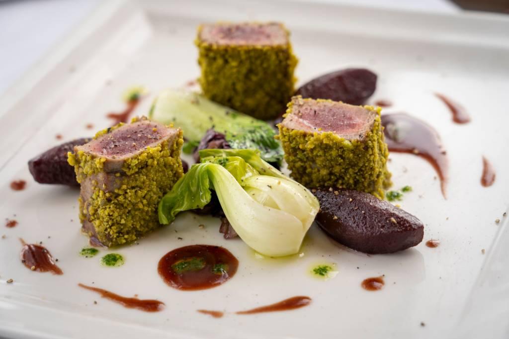 Prato com pedaços de atom em crosta de pistache, fatias de pêra e folhas verdes no restaurante Cipriani, do hotel Reid's Palace, na Ilha da Madeira