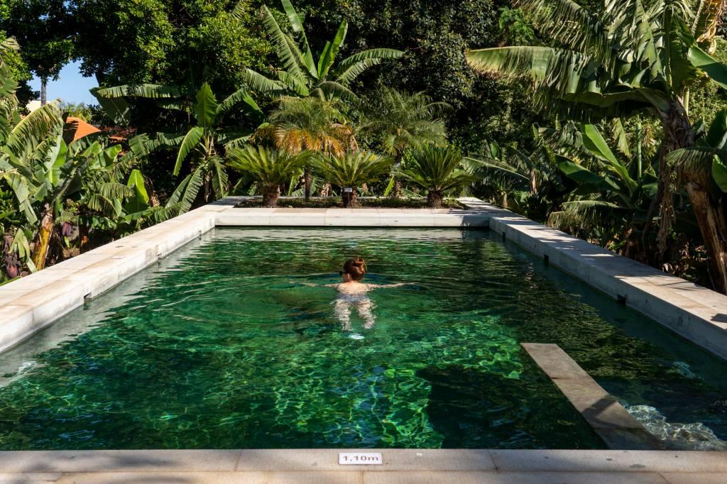 Mulher nadando em uma piscina cercada de bananeiras