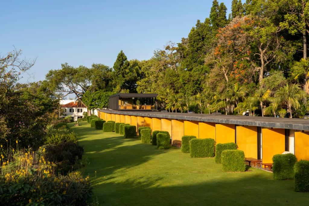 Construção com varandas amarelas e um gramado de um lado e árvores do outro